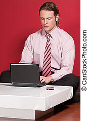 Concentrated businessman using a laptop while sitting on a...