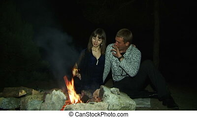 Romantic evening near the fire - Two young lovers sitting on...