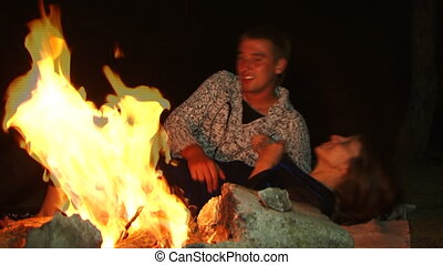 Romance flames - Two young lovers sitting on the night...