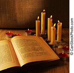 Open Old Book and Burning Candles