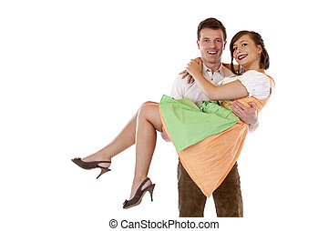 Bavarian man carries woman with dirndl on his arms and smiles.
