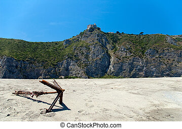 Old rusted anchor on the beach with Shrine of our Lady on background, Sicily, Italy