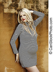 Beautiful eight months pregnant blond woman with curly hair in a black and white stripes fashion mini dress