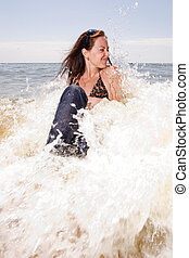 Young woman sits in water splashes at the beach
