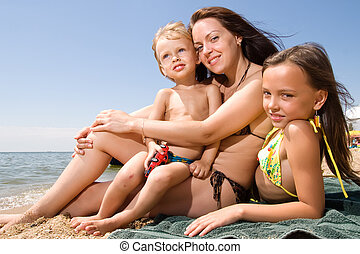 Young mom with kids at the beach resort - Mom and her...