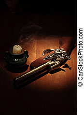 The End - Extinguished candle near ancient pistol on wooden...
