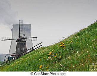 Old windmill with nuclear cooling towers in the back,...