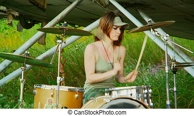 Girl loves to play drums - Beautiful girl in a cap sits and...