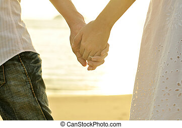 Holding Hands - Young adult male and female holding hands on...