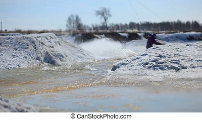 A snowboarder riding in water, spri - A sowboarder riding in...