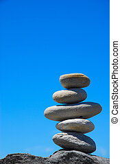 Nature zen - A pile of five big grey pebbles on a rock in...