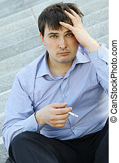 Businessman smokes - Young business man sitting on the...