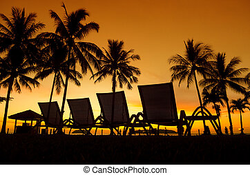 Tropical Sunset - Row deckchairs on beach at sunset, Tanjung...
