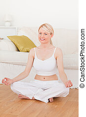 Young beautiful female doing yoga in the living room