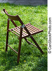 Wooden camp chair on green grass - Wooden camp stool on...