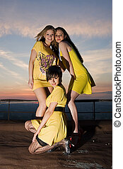 Three sexy young women in yellow dresses posing on a roof