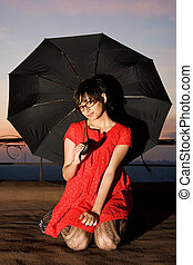 Attractive young lady sitting with an umbrella on the rooftop