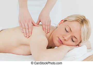 Closeup of young attractive blonde female receiving a back...