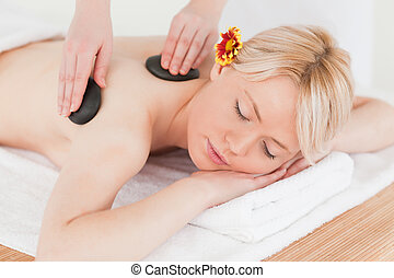 Young woman receiving a massage with hot stones in a Spa...