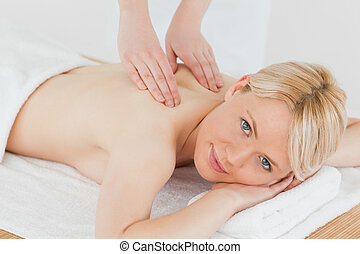 Closeup of young cute blonde woman receiving a back massage...