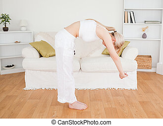 Good looking blonde woman stretching in the living room