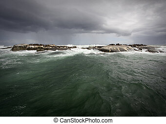 Stormy weather over the ocean with seal island on the...