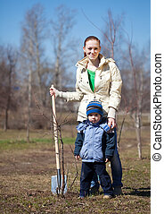 mother and son planting tree - mother and son with spade...