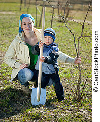 mother and son planting  tree outdoors