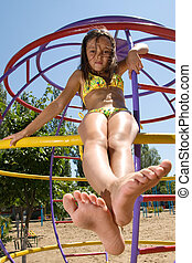 Little girl sitting at the playground on the beach - Little...