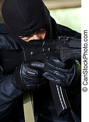 Armed soldier aiming the target - Trooper in black mask...
