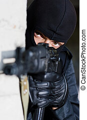 Soldier in black uniform with rifle - Gunman aiming his...