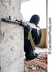 Armed soldier aiming the target - Man in black camouflage...