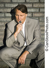 depressed businessman with phone - A depressed businessman...