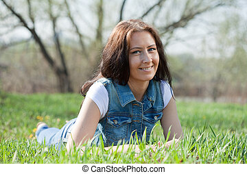 middle ages brunette woman  is relaxing in   park