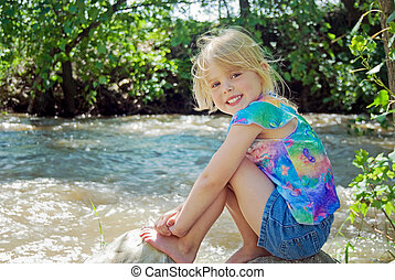 girl on river rock - Little blond girl on a rock by rushing...