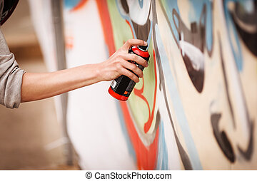 graffiti - young teen with paint spray makes urban art,...