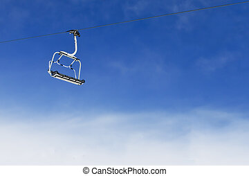 Ski lift chair on bright blue sky - Empty ski lift chair for...