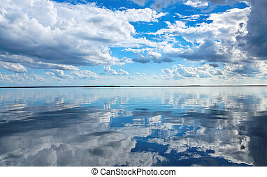 These water reflections of white cumulus clouds in a rich...
