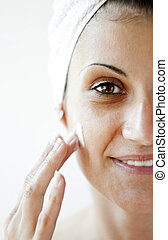 skin care - Beautiful young woman applying a creme on her...