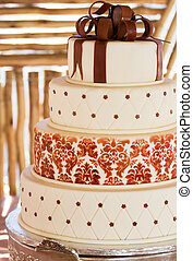 Layered white wedding cake with chocolate detail on silver...