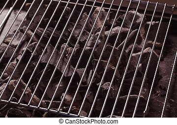 Charcoal under a barbecue grid