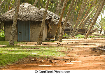 Fishing huts in Kerala India with fishing boat in the...