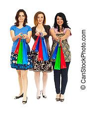 Three women giving shopping bags