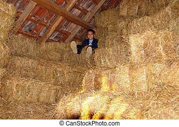 Boy on straw bales - boy sitting on straw bales in warehouse...