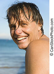 Forties man smiling on beach.