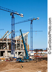 construction site with cranes and heavy equipment.