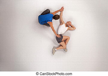streching man with personal trainer - Overhead view of...