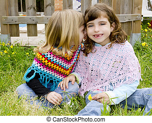 children sister girls whisper in ear meadow spring fence...
