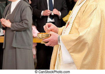 Catholic priest granting the Commun