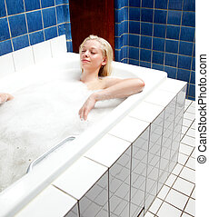 Relaxing Bath Woman - A woman soaking in a relaxing bath in...